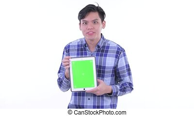 Happy young Asian hipster man showing digital tablet and looking surprised