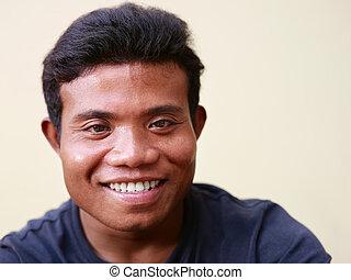 Happy young asian man looking at camera