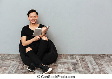 Happy young asian man sitting isolated over grey wall