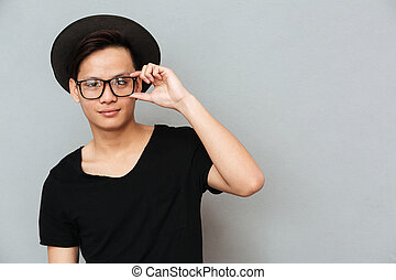 Happy young asian man standing isolated over grey wall
