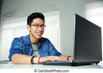 Happy young asian man working at office