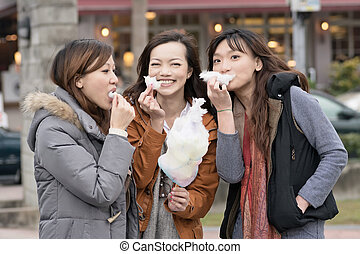 Happy young Asian woman eating cotton candy with her friends