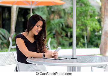 Happy young Asian woman sitting at outdoor cafe table reading text message on smart phone