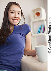 Happy young asian woman sitting on the couch holding mug