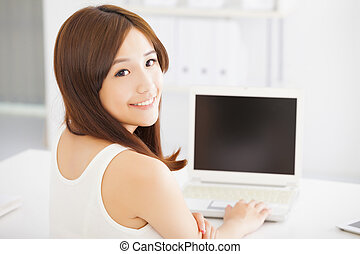 happy young asian woman using a laptop at home