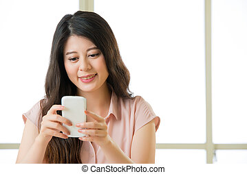 Happy young Asian woman using smart phone text messaging