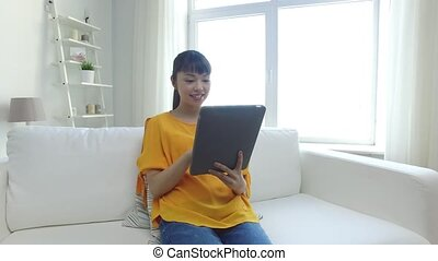 happy young asian woman with tablet pc at home