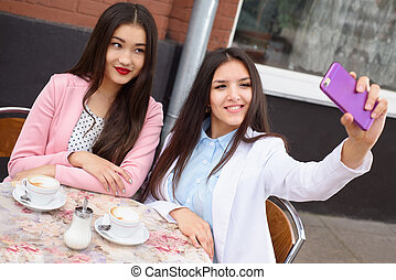 Happy Young asian women making selfie photo on smartphone outdoors