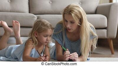 Millennial female babysitter teaching little girl writing letters.