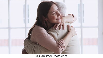 Happy young attractive woman visiting elderly senior father. Excited affectionate middle aged grey haired man greeting loving grownup daughter at home or retirement house, 2 generations reunion.