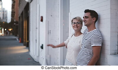 Happy young authentic romantic couple stand close together on a date by white building wall in evening Soho, New York.