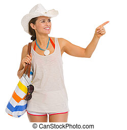 Happy young beach woman in hat pointing on copy space