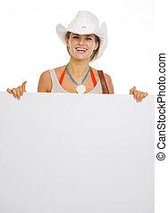 Happy young beach woman in hat showing blank billboard