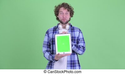 Happy young bearded hipster man showing digital tablet and looking surprised