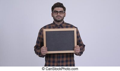 Happy young bearded Indian hipster man holding blackboard