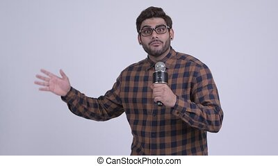Happy young bearded Indian hipster man presenting something with microphone