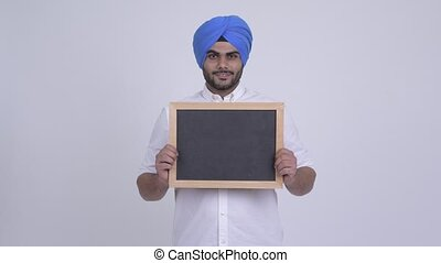 Happy young bearded Indian Sikh man holding blackboard