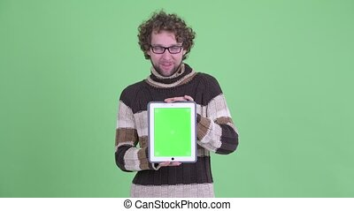 Happy young bearded man showing digital tablet and looking surprised