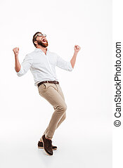 Happy young bearded man showing winner gesture.