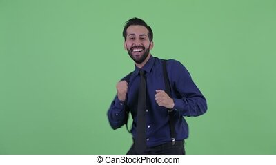 Happy young bearded Persian businessman dancing - Studio...
