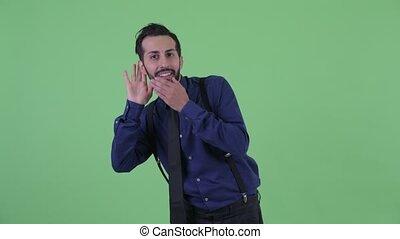 Happy young bearded Persian businessman listening - Studio...