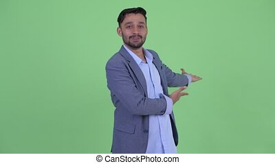 Happy young bearded Persian businessman presenting something...