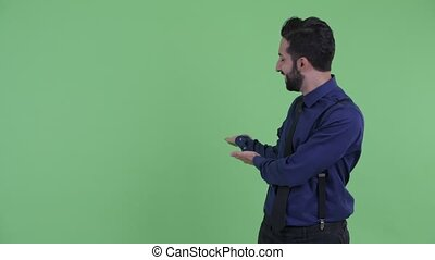 Happy young bearded Persian businessman showing to back -...