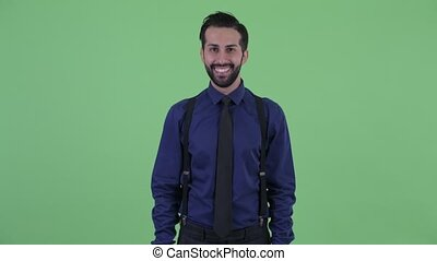 Happy young bearded Persian businessman smiling - Studio ...