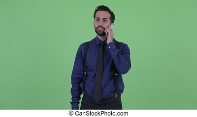Happy young bearded Persian businessman talking on the phone...