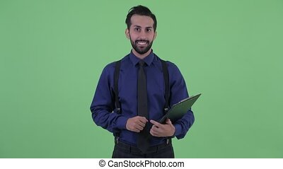 Happy young bearded Persian businessman talking while...