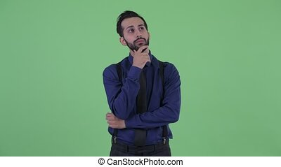 Happy young bearded Persian businessman thinking - Studio...