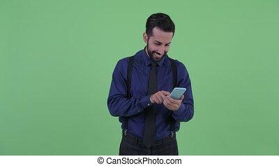 Happy young bearded Persian businessman using phone - Studio...