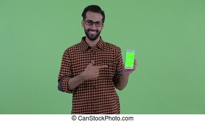 Happy young bearded Persian hipster man showing phone and giving thumbs up