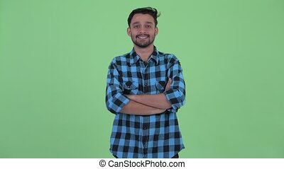 Happy young bearded Persian hipster man smiling with arms crossed