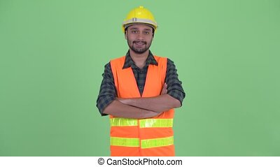Happy young bearded Persian man construction worker smiling with arms crossed