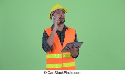 Happy young bearded Persian man construction worker using phone and digital tablet