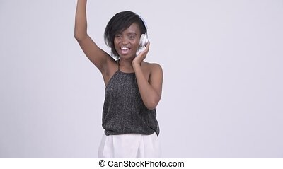Happy young beautiful African woman dancing and listening to music