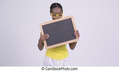 Happy young beautiful African woman holding blackboard -...