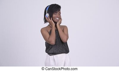 Happy young beautiful African woman listening to music and...