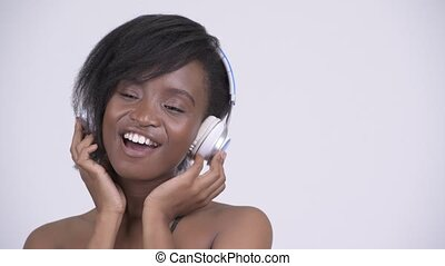 Happy young beautiful African woman listening to music