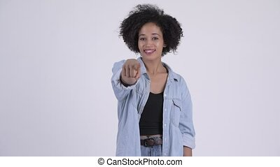 Happy young beautiful African woman pointing at camera