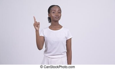 Happy young beautiful African woman pointing up