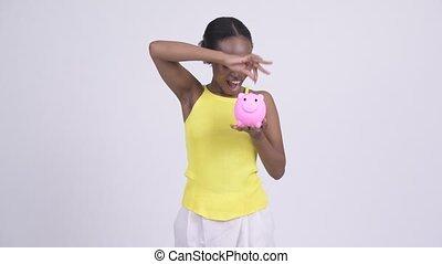 Happy young beautiful African woman showing piggy bank -...