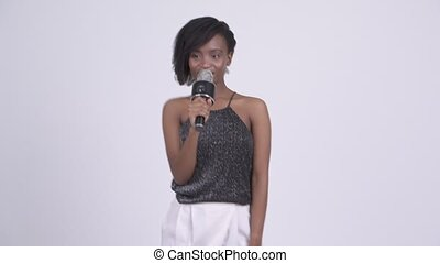 Happy young beautiful African woman singing with microphone