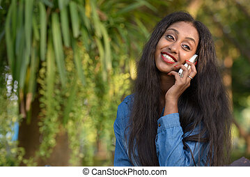 Happy young beautiful African woman talking on the phone at the park