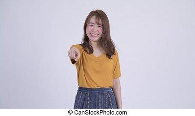 Happy young beautiful Asian woman pointing at camera