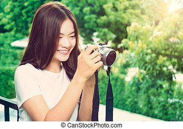 happy young beautiful asian woman smiling and taking picture with her camera