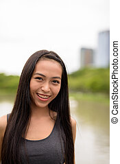 Happy young beautiful Asian woman smiling at the park