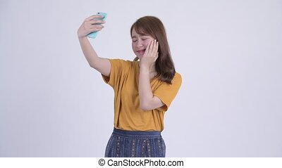 Happy young beautiful Asian woman taking selfie