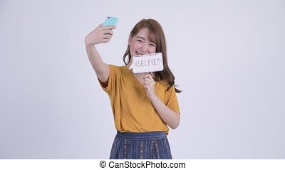 Happy young beautiful Asian woman taking selfie with paper sign